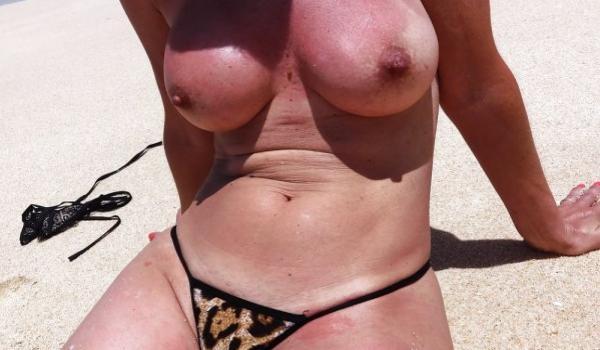 Amadora dos seios empinados tomando banho de sol